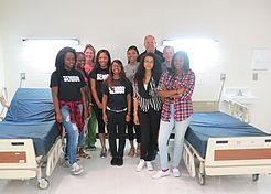 Students pose with donated hospital beds